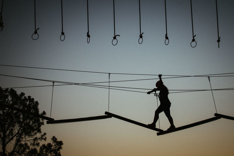 Low angle view of silhouette girl walking on rope against sky