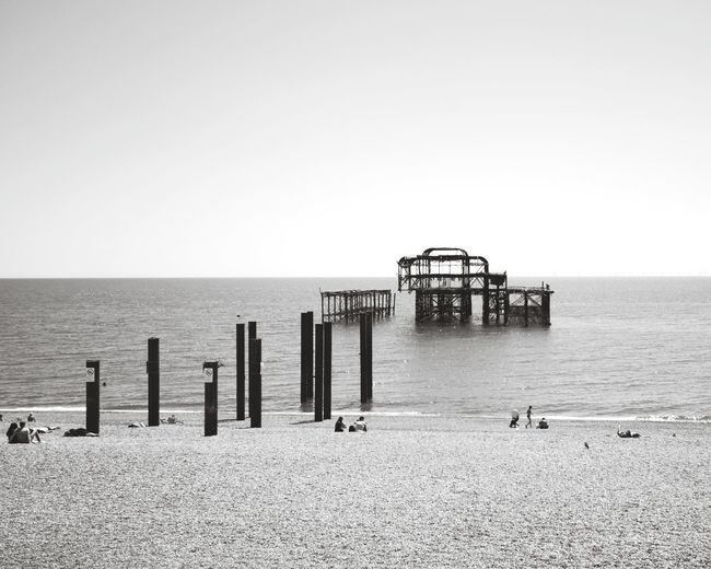 Old pier in Brighton Blackandwhite Black & White Blackandwhite Photography Black And White Collection  Citiyscape The Week on EyeEm Black And White Travel Destinations Travel Landscape Landscape_Collection Black&white Water Sea Beach Groyne Sand Clear Sky Sky Horizon Over Water Wooden Post Seascape Pier Beach Hut Coastline Calm Ocean Wave Sandy Beach Beach Umbrella Sand Dune Tranquil Scene Parasol