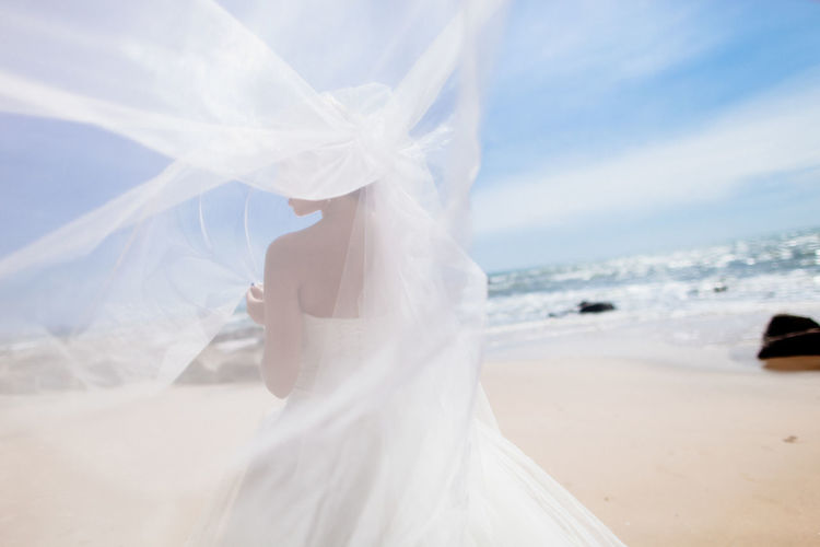 bride on beach luxury resort relaxing in Asia Adult Beach Bride Bridegroom Celebration Ceremony Close-up Day Groom Human Body Part Life Events Low Section Nature One Person Outdoors People Real People Sand Sea Sky Veil Wedding Wedding Dress Women Young Adult