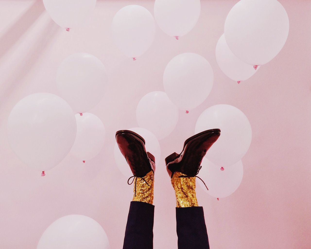 Low section of man with balloons against pink wall during party