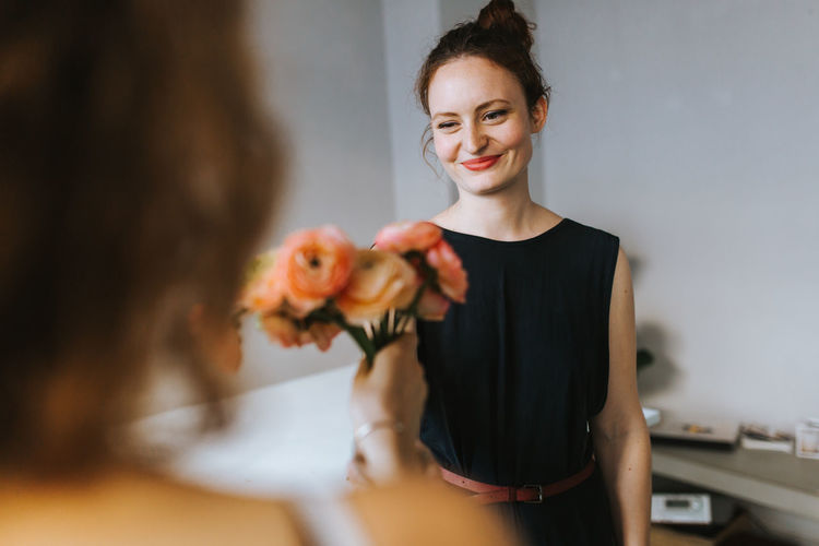 Smiling florist looking at customer with flowers