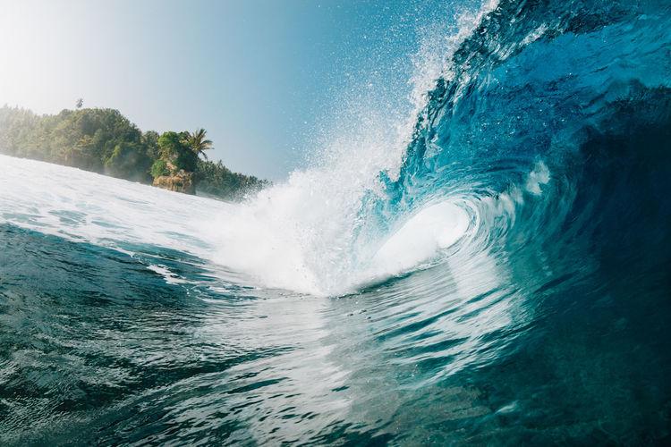 Waves splashing in sea against clear sky