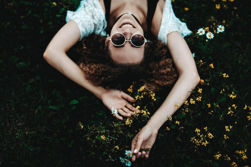 Young curly woman laying on green grassin the sunglasses and smiling.
