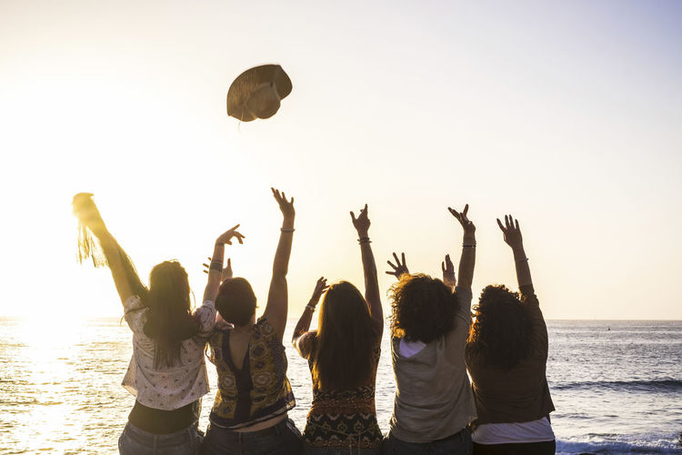 Summer and happiness for travel and freindship concept with group of happy girls viewed from rear enjoying and celebrating the sunset and the sea together launching hat and giving up Sky Group Of People Water Real People Leisure Activity Sea Lifestyles Beach Togetherness Sunset Friendship Women Enjoyment Nature Arms Raised Land Fun People Human Arm Teenager Rear View Emotion Five People Horizon Over Water Ocean Concept Summer Happiness Enjoying Life Launch Hat Positive Vibes Caucasian