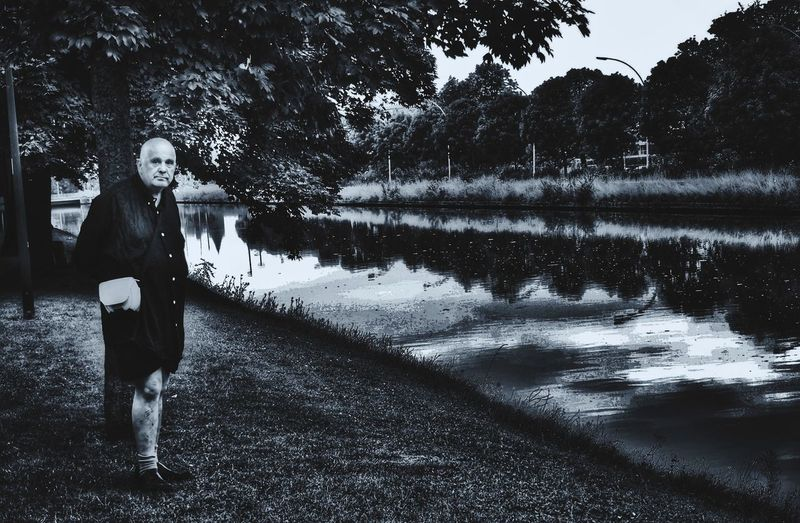 Man standing by lake against trees
