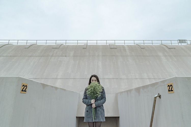 Young woman with flower bouquet standing against surrounding wall