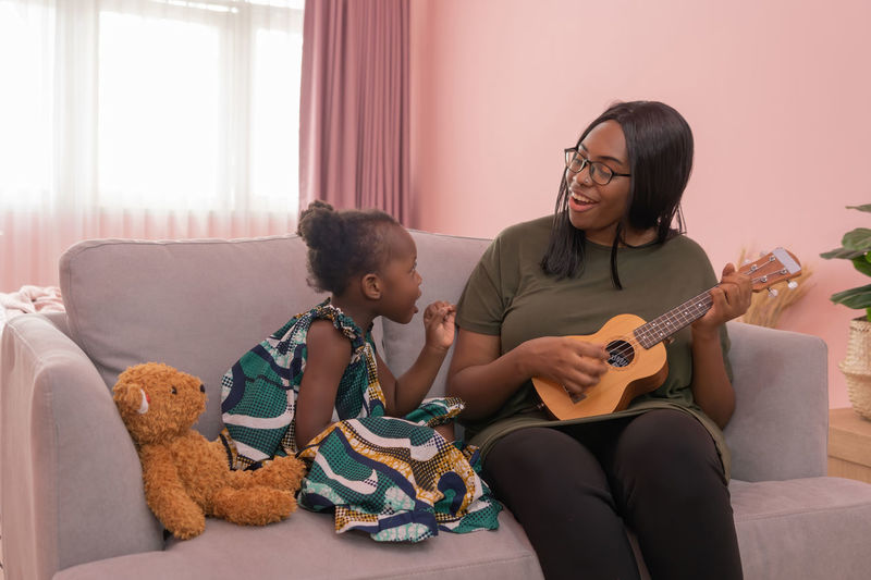 Mother playing guitar while sitting with daughter at home