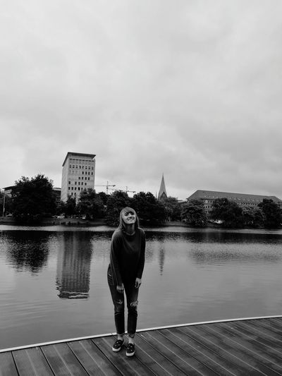 Portrait of smiling young woman standing on jetty over lake against cloudy sky