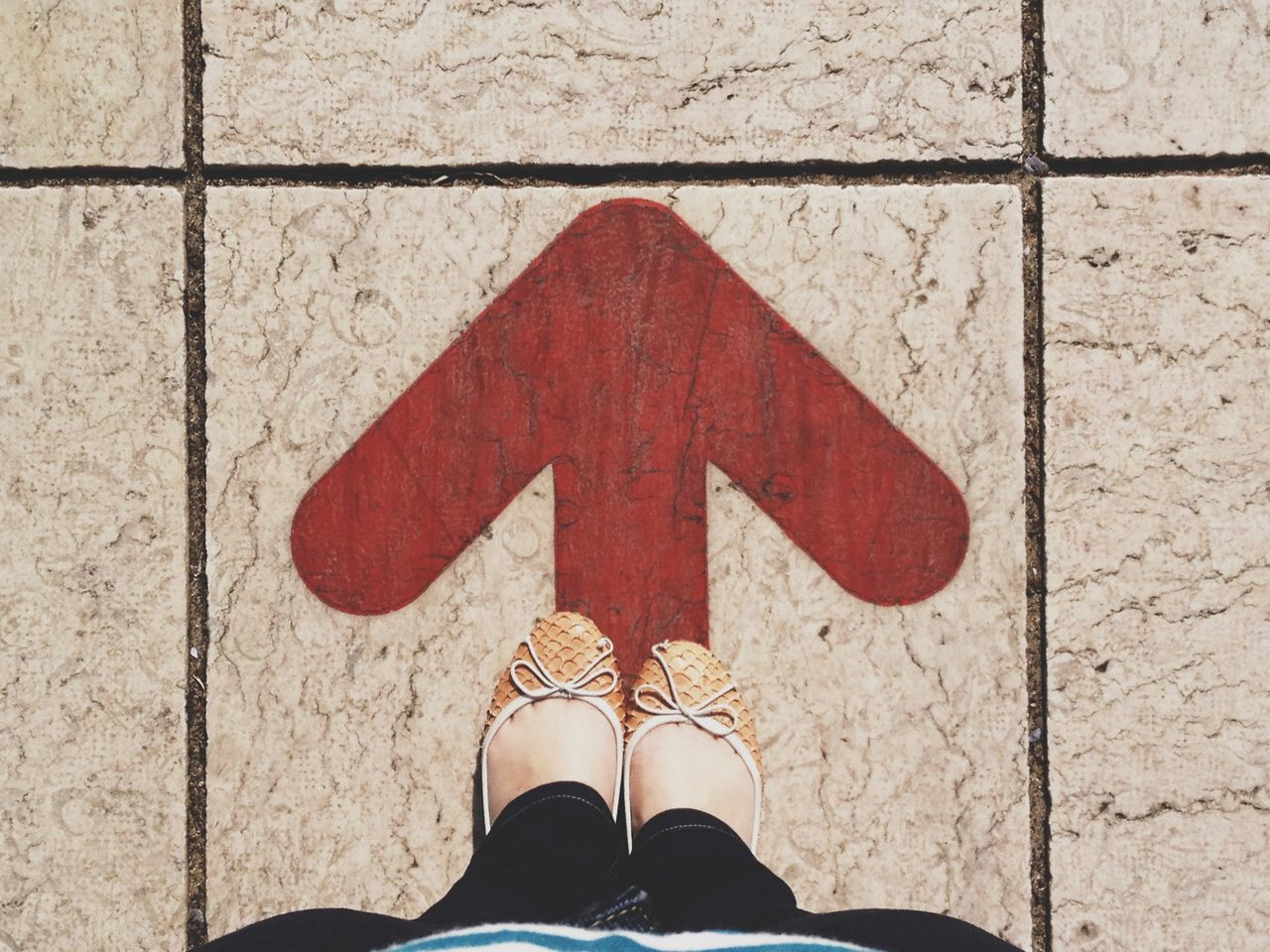 Low section of woman standing arrow sign