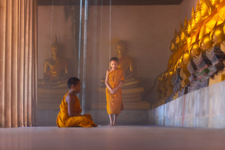 Side view of boy praying in buddhist temple