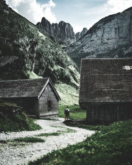 The alps are massive compared to us little humans. Mountain One Person Nature House Mountain Range Landscape Scenics - Nature Environment Real People Outdoors Beauty In Nature Stone Wall Land Alpstein, Switzerland Scale  Ebenalp Fälensee Switzerland Switzerlandpictures Moody Sky Moody