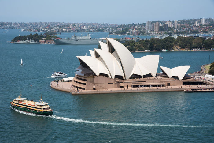 Sydney,NSW,Australia-November 20,2016: Elevated view over the Sydney Opera House at Bennelong Point in Sydney, Australia 20th Century Architecture Australia Cityscape Harbour Sydney Cove Sydney Opera House Tourist Tourist Attraction  Transportation Arts Culture And Entertainment Bennelong Point Boat Building Exterior Elevated View Expressionist Landmark Military Motion Nautical Vessel Ship Sydney Travel Destinations Wake Water