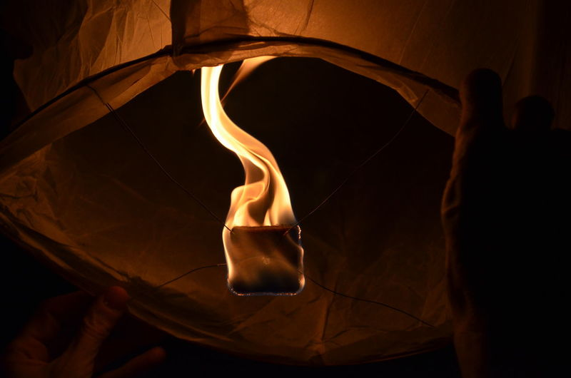 Low angle view of lit paper lantern at night