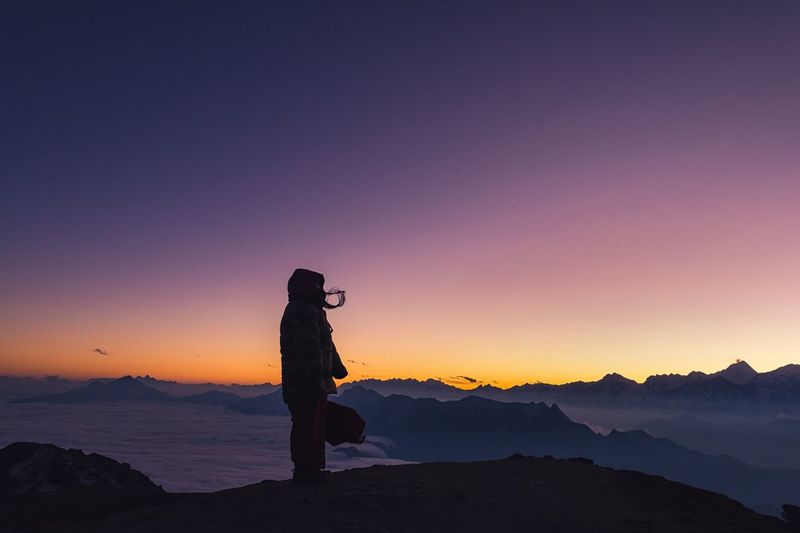 Silhouette Person Standing On Mountain Against Sky During Sunset