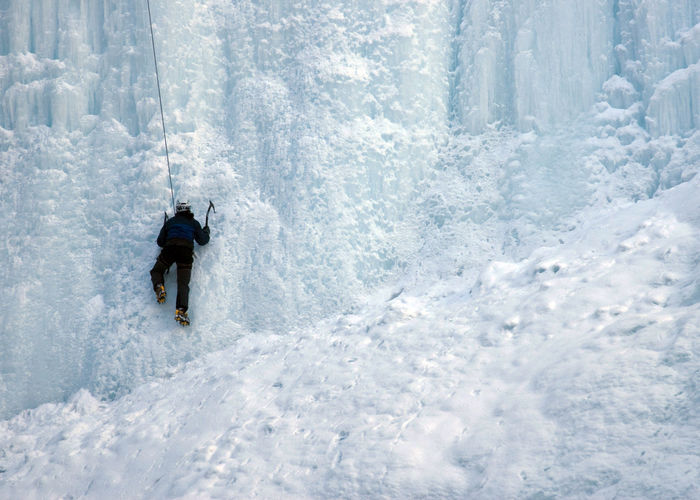 Rear View Of Person Climbing Wall Of Ice