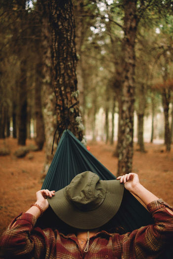 Midsection of woman with umbrella against trees in forest