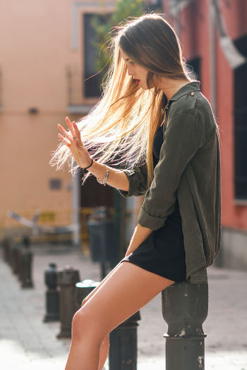 Portrait of blonde girl moving her amazing long hair Adult Beautiful Woman City Day Focus On Foreground Hair Hairstyle Holding Leisure Activity Lifestyles Long Hair One Person Outdoors Real People Side View Three Quarter Length Women Young Adult Young Women