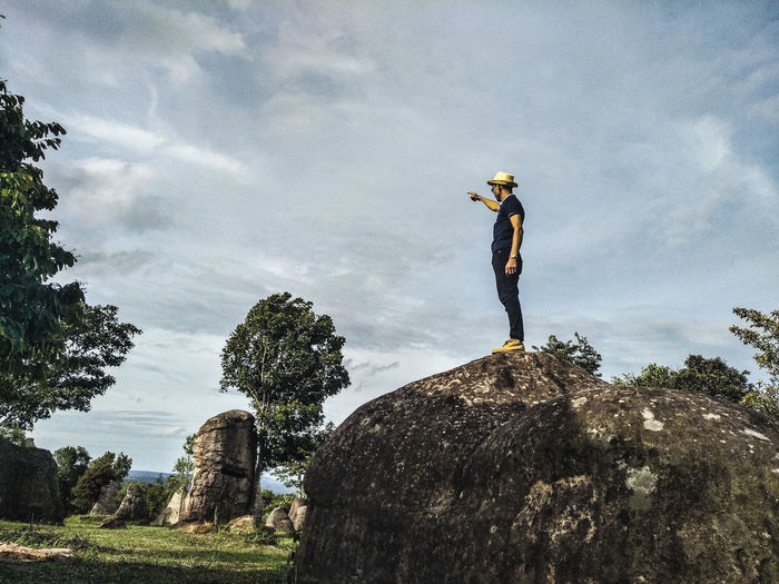 Low angle view of man standing on rock