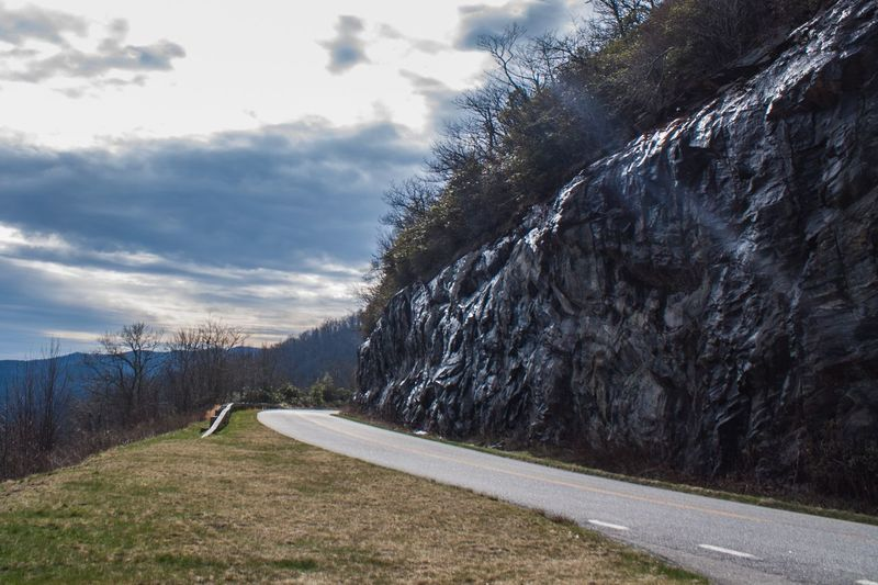 Road by cliff against sky