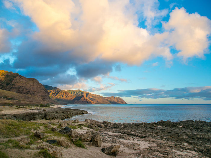 Scenic view of sea by rocky mountains against cloudy sky during sunset at oahu