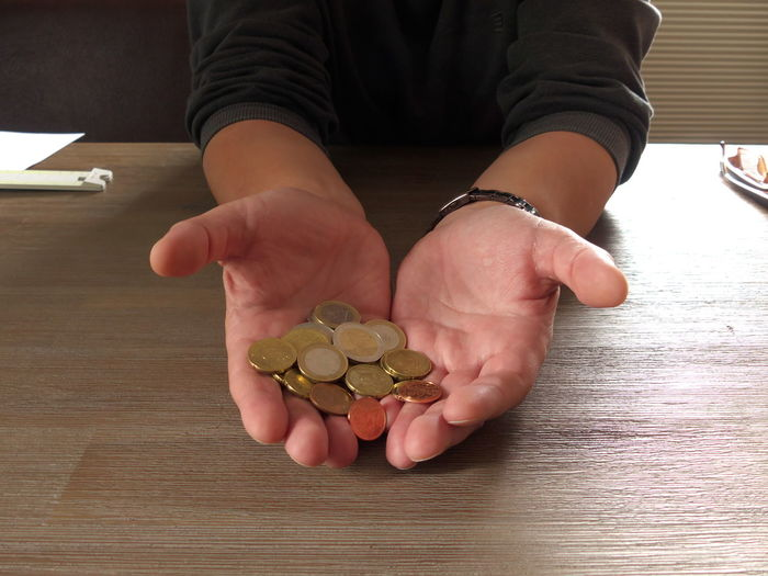 Midsection of person holding coins on table