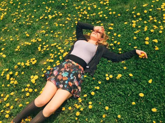 High angle view of beautiful woman resting on field surrounded by yellow flowers