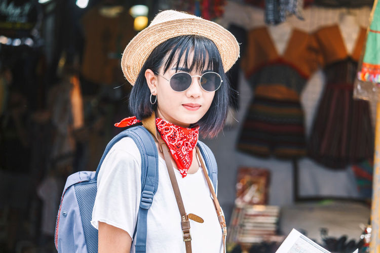 Portrait of young woman wearing hat and sunglasses in city