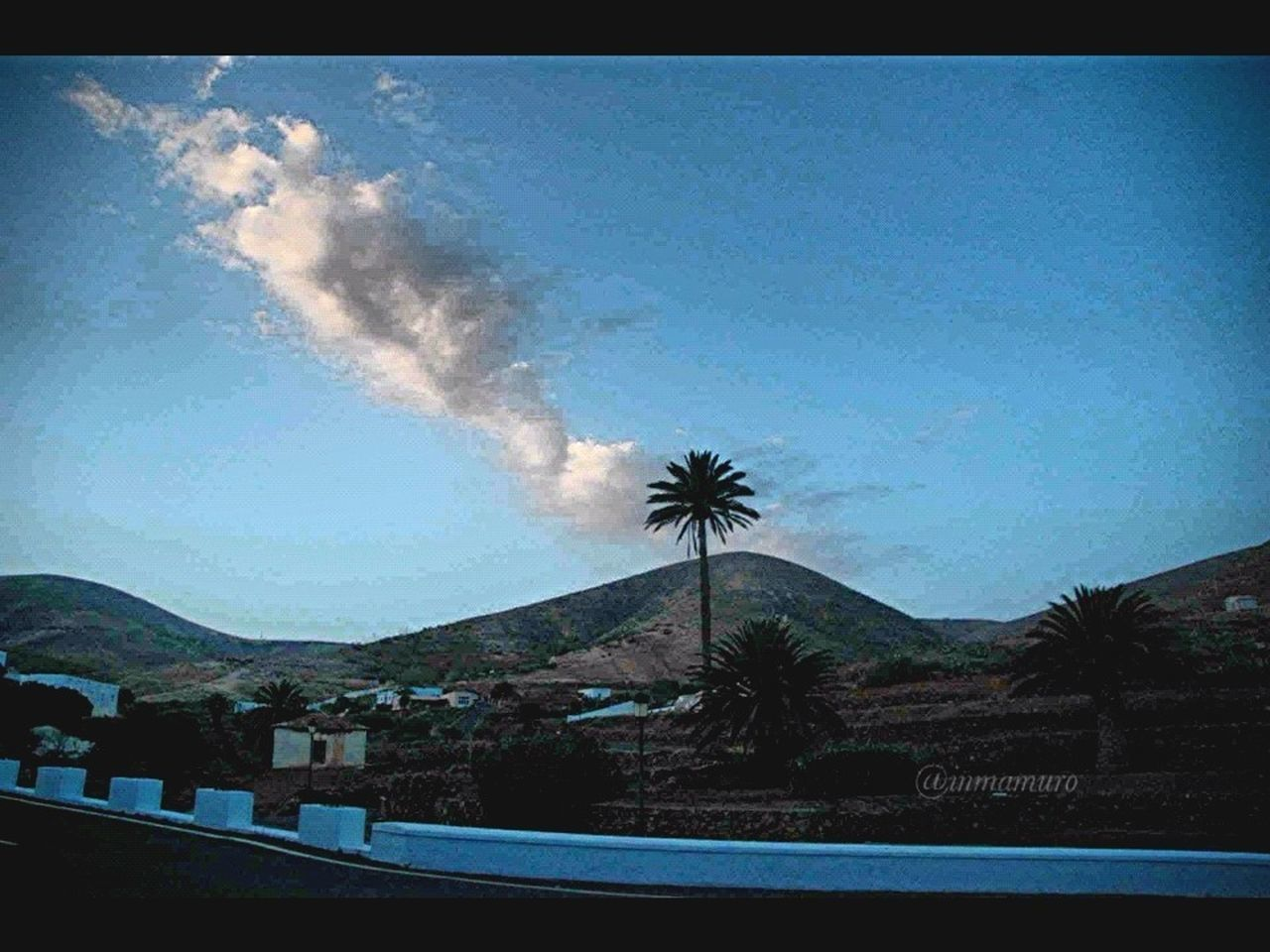tree, sky, palm tree, mountain, no people, outdoors, nature, day, blue, landscape, built structure, beauty in nature, architecture, building exterior, scenics, vapor trail