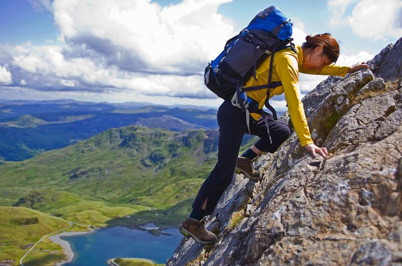 Man standing on rock against mountain range