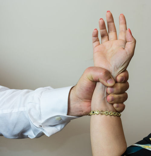 Cropped image of man gripping woman hand
