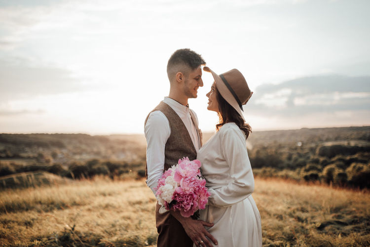 Couple standing on land against sky