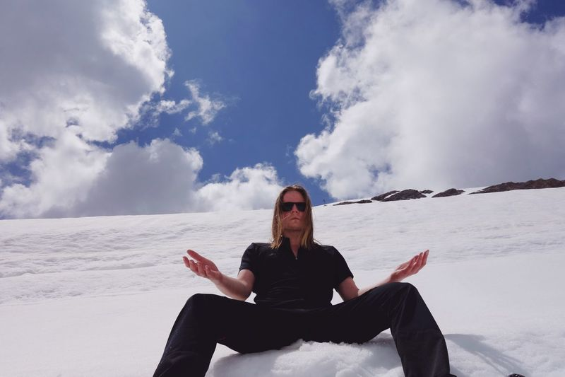 Low Angle Portrait Of Man Sitting On Snowcapped Mountain Against Cloudy Sky