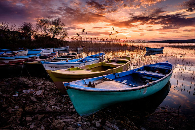 Boats on the lake under sunset. Nautical Vessel Moored Water Mode Of Transportation Sky Transportation Cloud - Sky Sunset Nature Tranquility Land Beach Scenics - Nature No People Tranquil Scene Rowboat Lake Beauty In Nature Plant Outdoors Fishing Boat Recreational Boat