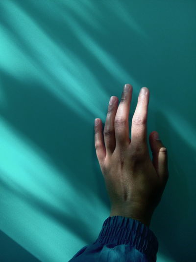 Close-up of human hand by wall during sunny day