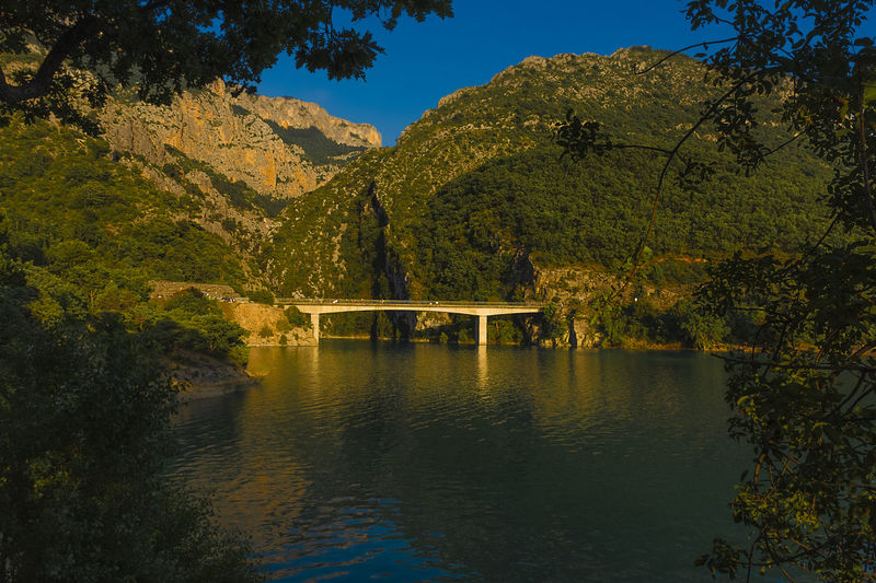 Bridge over river against trees and mountains