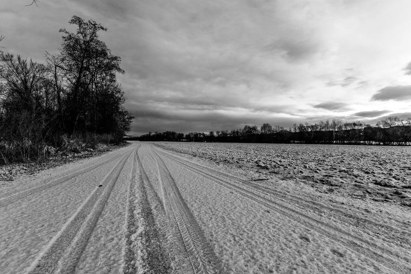 Tire tracks on agricultural field against sky during winter
