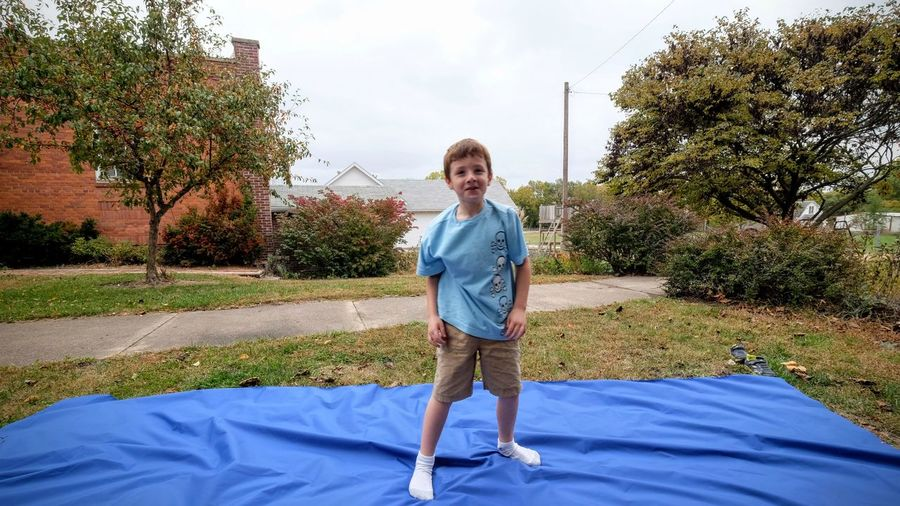 Full length portrait of smiling boy standing in park against sky