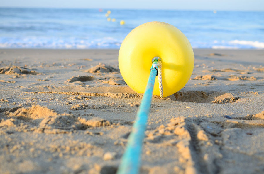 Beach Beachphotography Boya Buoy Close-up Day Marina No People Outdoors Sand Sea Selective Focus Shore Surface Level Tranquility Water Yellow