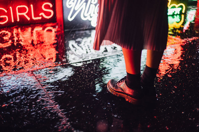 Low section of girl standing on wet footpath at night
