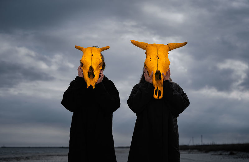 People with yellow mask standing by sea against cloudy sky