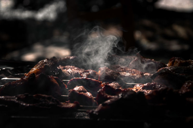 Steam emitting from meat on barbecue grill