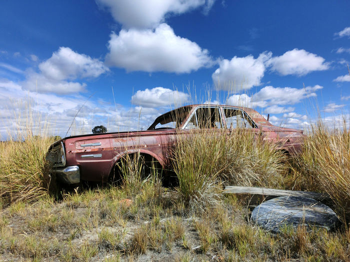 Abandoned car on field against sky