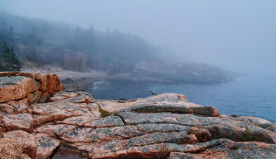 Rocks by sea against sky during foggy weather