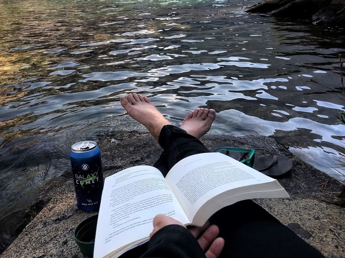 Low section of woman reading book by lake
