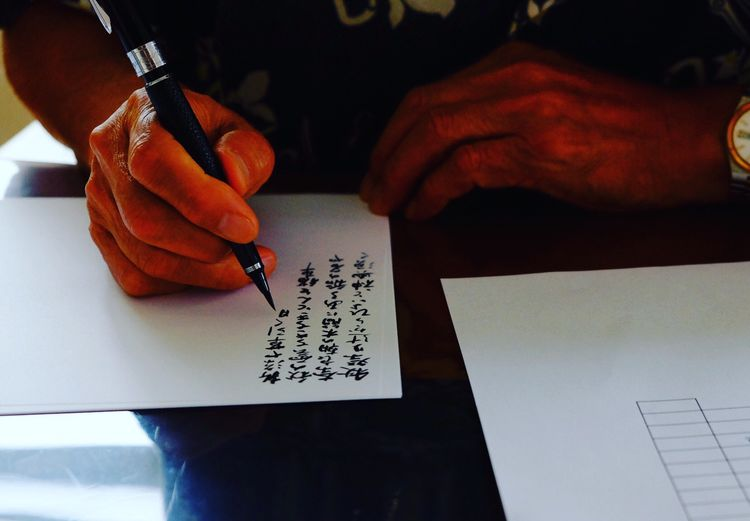 Person Holding Text Western Script Book Communication Indoors  Human Finger Part Of Paper Desk Focus On Foreground Handwriting  Pen Message Note 俳句 緑寿の嗜み Father