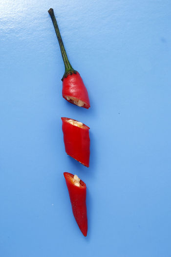 sliced red chili pepper Food Spice Spicy Food Hot Ingredient Flavor Taste Cut SLICE Sliced Seed Red Vegetable Studio Shot Red Colored Background Close-up Food And Drink Red Chili Pepper Chili  Jalapeno Pepper Chopping Board Spice Pepper Chili Pepper Pepper - Vegetable Red Bell Pepper