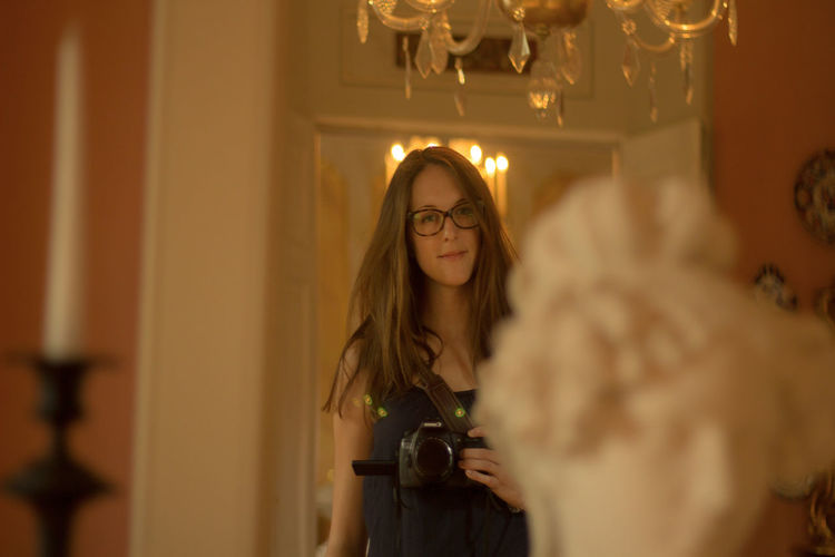 Beautiful young woman holding camera while standing at home