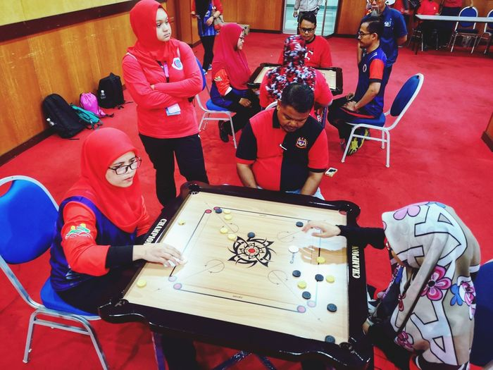 Play carrom Sport Indoor Game Carromboard Carrom Attraction Colorful Serious Face Togetherness