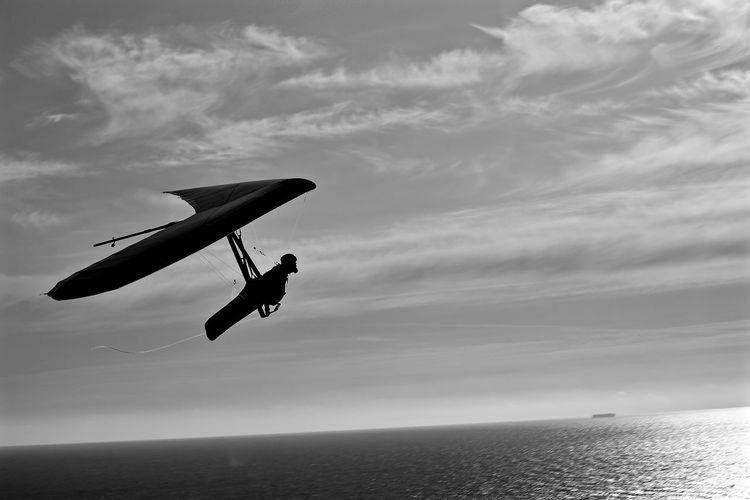 Silhouette man hang-gliding above sea