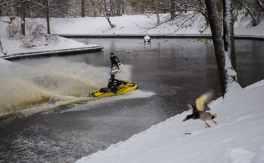 High angle view of people on jet skis on river during winter